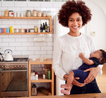 Portrait Of Smiling Mother Holding Sleeping Baby Son In Kitchen